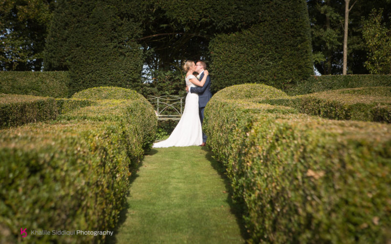 Bride and groom in sculpted garden